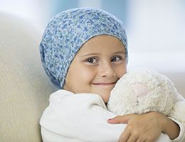 A child battling cancer smiles while hugging a stuffed animal.