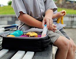 A child pulls an epi pen from a lunchbox.