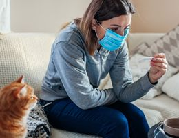 A woman in a face masks sits on a couch looking at a thermometer. A cat supervises.