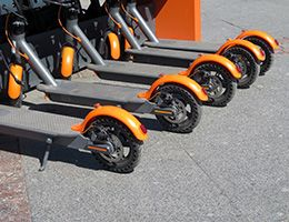 A row of orange and gray e-scooters.