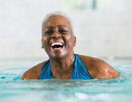 A laughing woman standing in a pool.