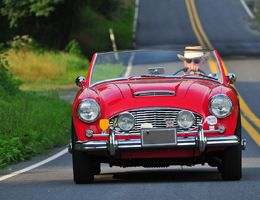 A man in a Panama hat drives a red convertible.