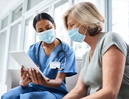A patient and a healthcare provider look at a tablet together.
