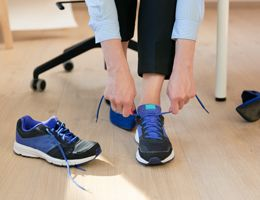 A woman swaps heels for walking shoes in an office setting.