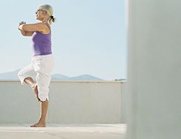 A woman practicing yoga outside.