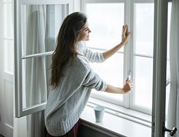 A woman holds the latch of a window.
