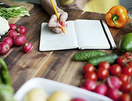 A hand makes notes in a notebook on a produce-covered table.