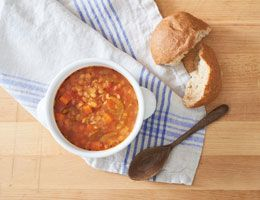 Lentil soup with crusty bread and a wooden spoon
