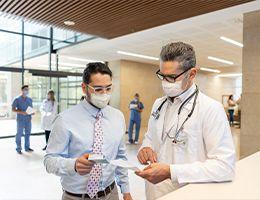 A man and a healthcare provider discuss a box of medicine.