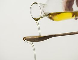 Olive oil pouring over a wooden spoon.