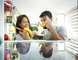 Two happy young adults holding produce in front of a refrigerator.