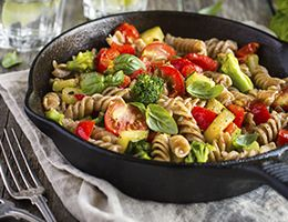 A cast iron skillet filled with pasta and vegetables.