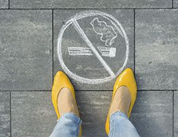 A woman is standing next to a no smoking symbol drawn on a sidewalk.