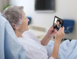 A woman in a hospital bed video chats on a smartphone.