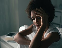 A woman sits in a dark bedroom with her eyes closed.