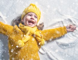 A girl in a yellow sweater, hat and scarf makes a snow angel.