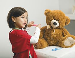 A little girl giving her teddy bear a checkup.