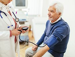 A man gets his blood pressure checked by a doctor.