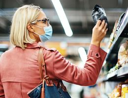 A woman wearing a face mask looks at a package label in a grocery store.