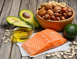 Fish, oil, avocados, seeds and nuts on a wood table.