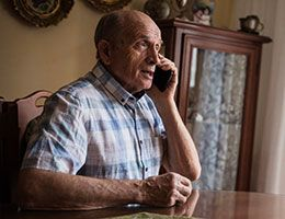 An older man sits at a table and talks on a phone.