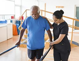 A physical therapist helps a man walk between parallel bars.