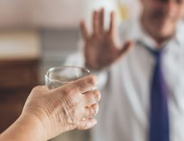 A hand holds out a glass to a man gesturing no in the background.