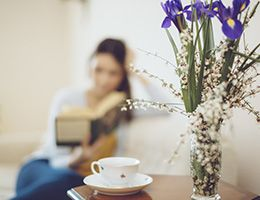 A woman is sitting alone reading a book. A tea cup and flowers are nearby.