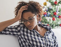 A sad woman with a Christmas tree in the background.