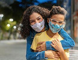A woman hugs a child, both wearing face masks.