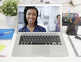A doctor video chatting on a laptop screen.
