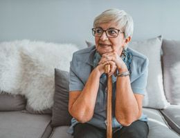 An older woman sitting on a couch and leaning on a cane.