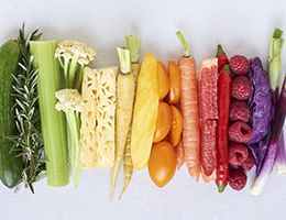An assortment of fresh fruits and vegetables arranged to create a rainbow of colors.