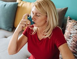 A woman sits on a couch and uses an inhaler.
