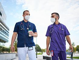 Two masked healthcare workers walking outside.