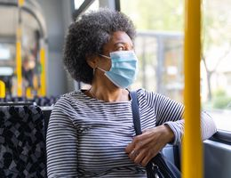 A woman wearing a face mask looks out the window of a bus.
