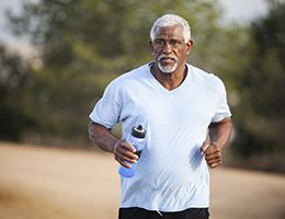 A middle-aged man jogging outside.