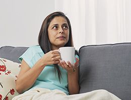 A woman on a couch holding a mug.