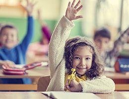 Grade-schooler raises her hand in a classroom.