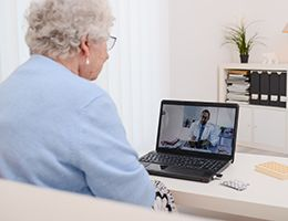 A woman looks at a laptop with a clinician on screen.