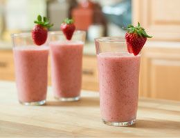3 full glasses of strawberry shake garnished with strawberries