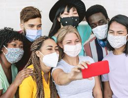A group of teens in face masks pose for a selfie.