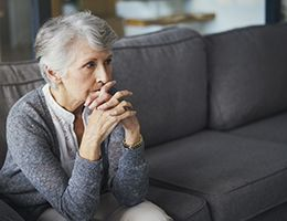An older woman sits on a couch looking sad.