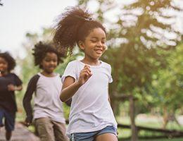 Three kids running outside.