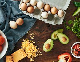 Shredded cheese, sliced avocado, and eggs.