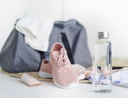 A bottle of water in front of a gym bag, shoes, etc.
