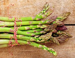 A bunch of asparagus tied with red and white string.
