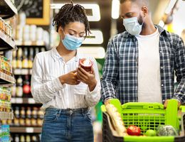 A couple in a grocery store wearing face masks.