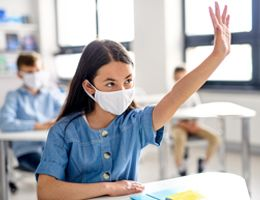 A girl wearing a face mask raises her hand in a classroom.