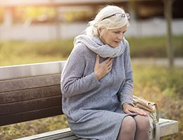 A woman sitting on a bench with her hand over her heart.